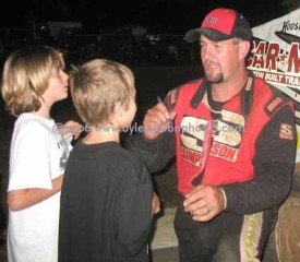 Photo of Jeremiah signing autographs for two young fans after another victory at Tri-City in 2007.